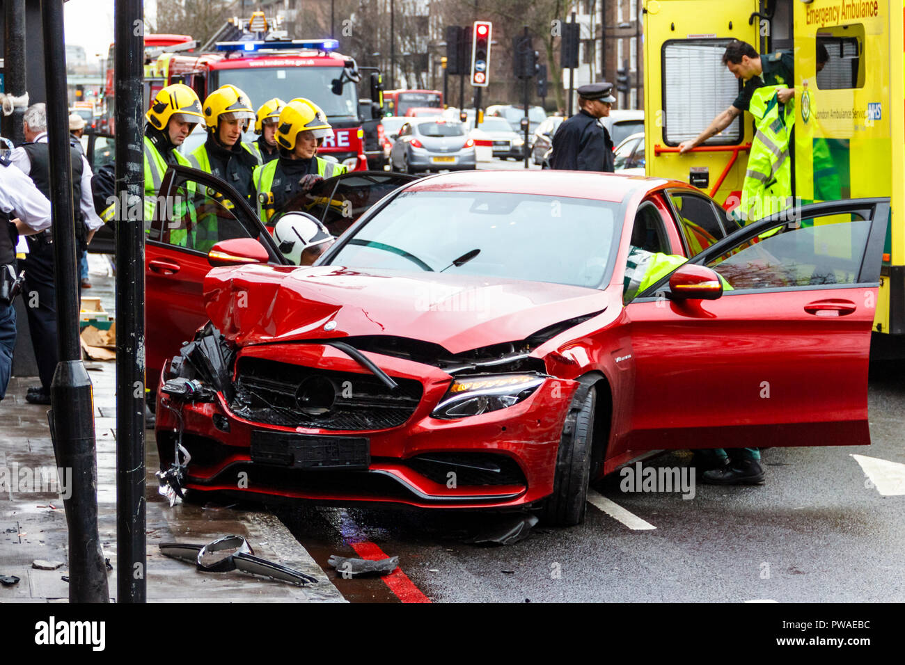 Firefighters, paramedics and police attend a road traffic incident involving a red car in Holloway, London, UK in January 2016. Luckily no one was hurt - Stock Image