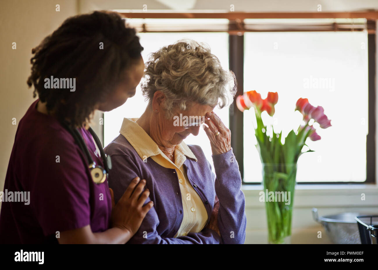 Young nurse comforting a grieving senior woman. Stock Photo