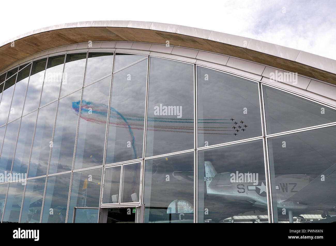 american-air-museum-at-imperial-war-museum-duxford-cambridgeshire-uk-red-arrows-display-team-reflected-in-glass-frontage-of-building-PWN6KN.jpg