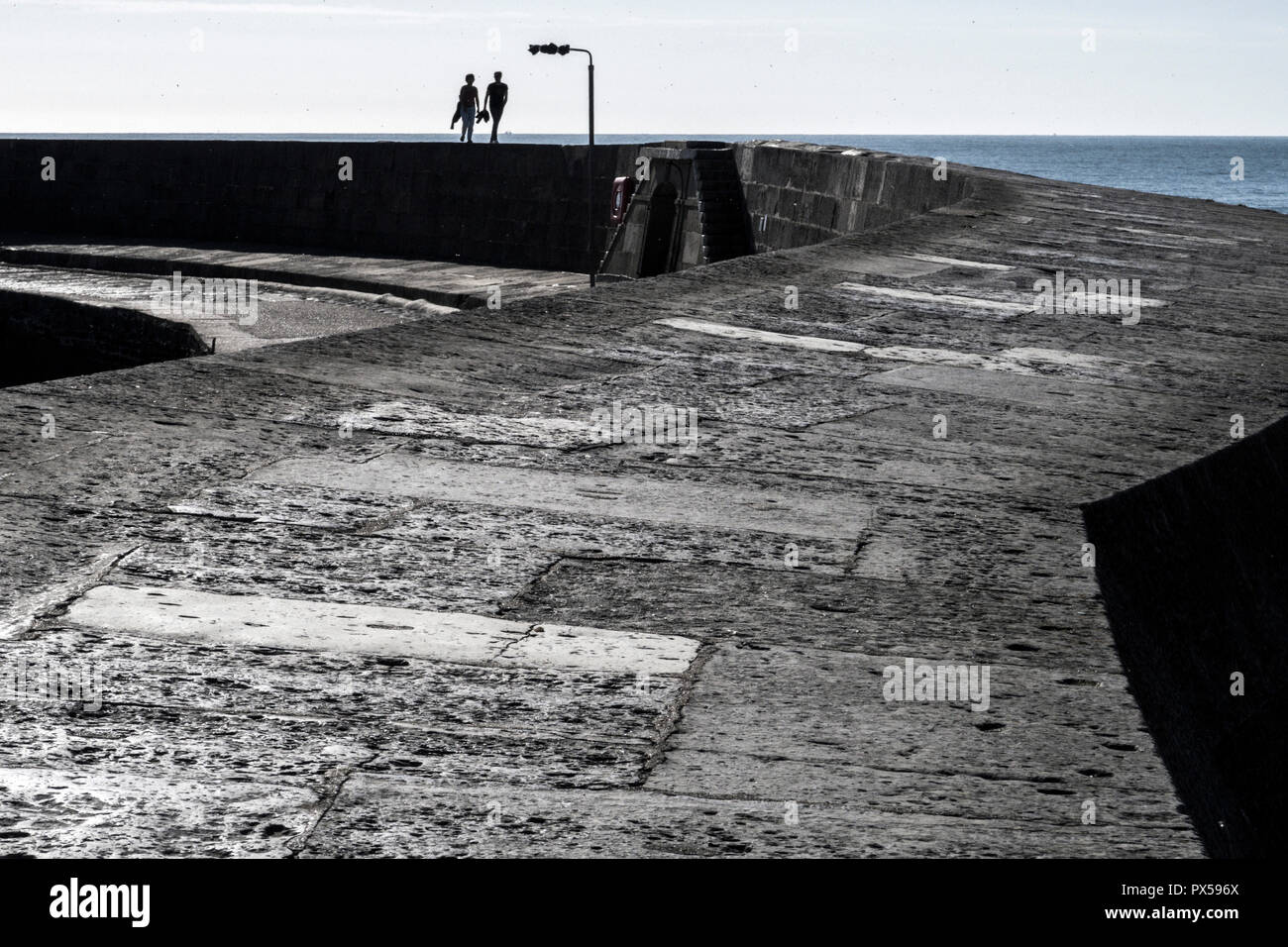 A couple walk along the Cobb, Lyme Regis, Dorset, UKStock Photo