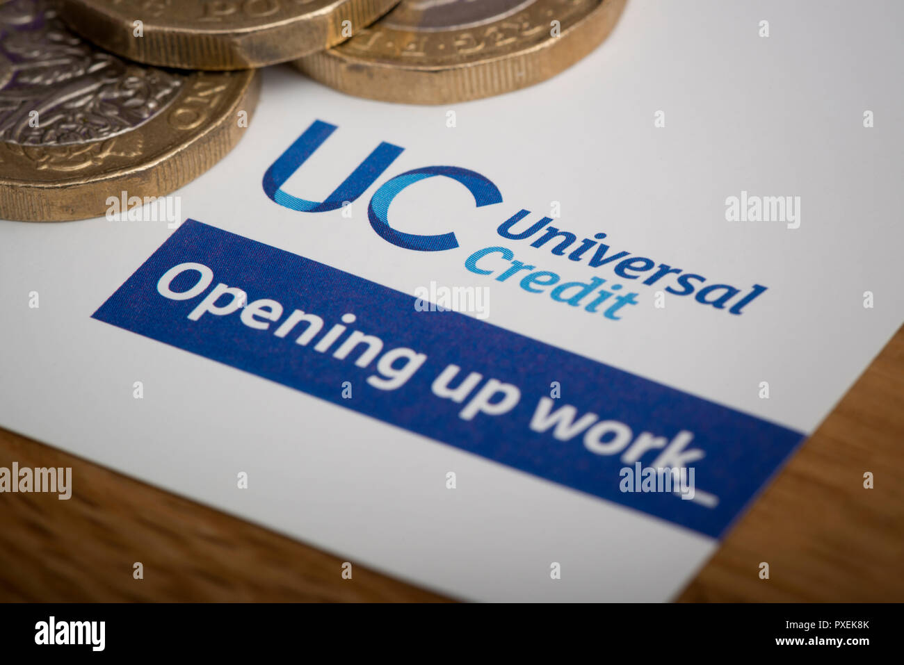 A piece of stationery featuring the Universal Credit logo, rests on a table along with some £1 coins. Stock Photo