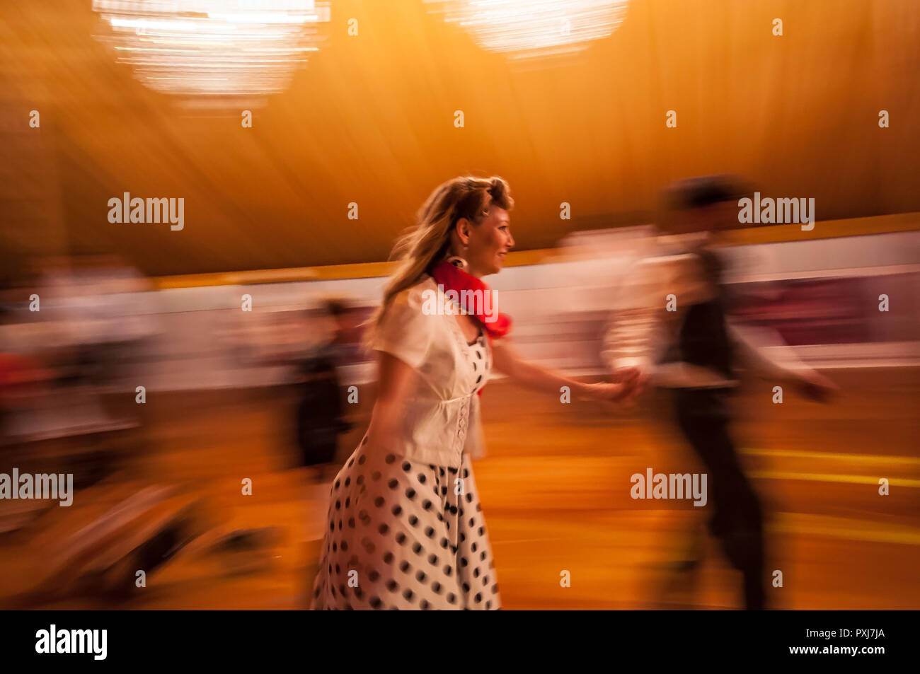 female-roller-skater-in-vintage-period-dress-at-the-goodwood-revival-1950s-era-costume-moving-fast-with-motion-blur-highlighting-face-PXJ7JA.jpg