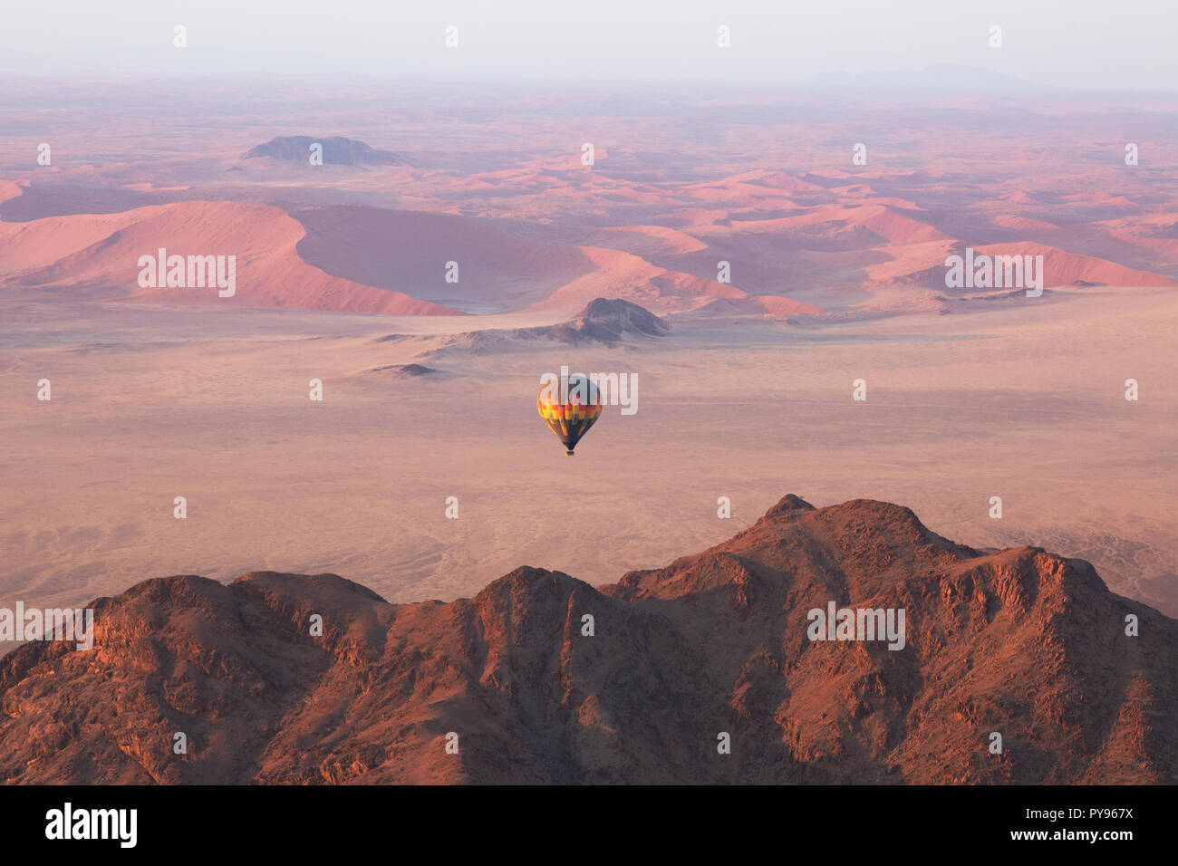 namibia-travel-hot-air-balloon-at-sunrise-over-the-namib-desert-example-of-adventure-travel-namibia-africa-PY967X.jpg