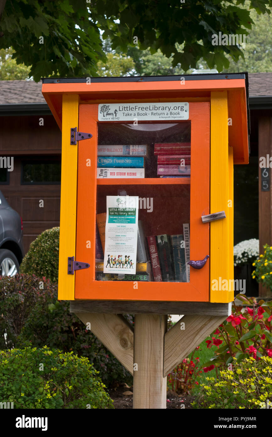 """Little Free Library"" box with books for sharing in a Canadian residential neighbourhood. Stock Photo"