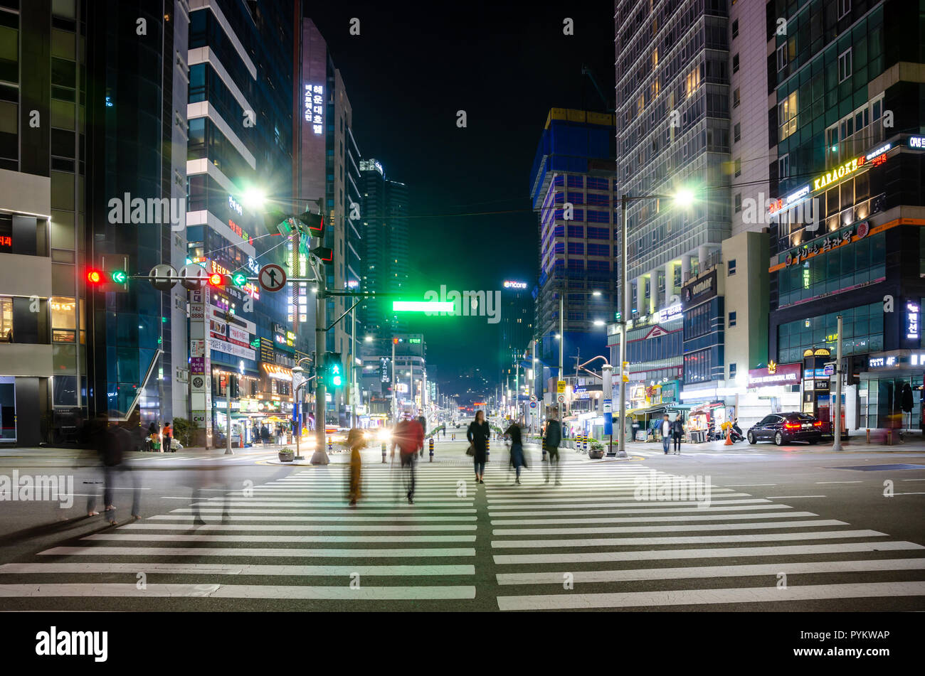 people-cross-a-pedestrian-crossing-at-night-in-haeundae-busan-south-korea-behind-the-street-is-full-or-bright-lights-shining-in-the-dark-PYKWAP.jpg