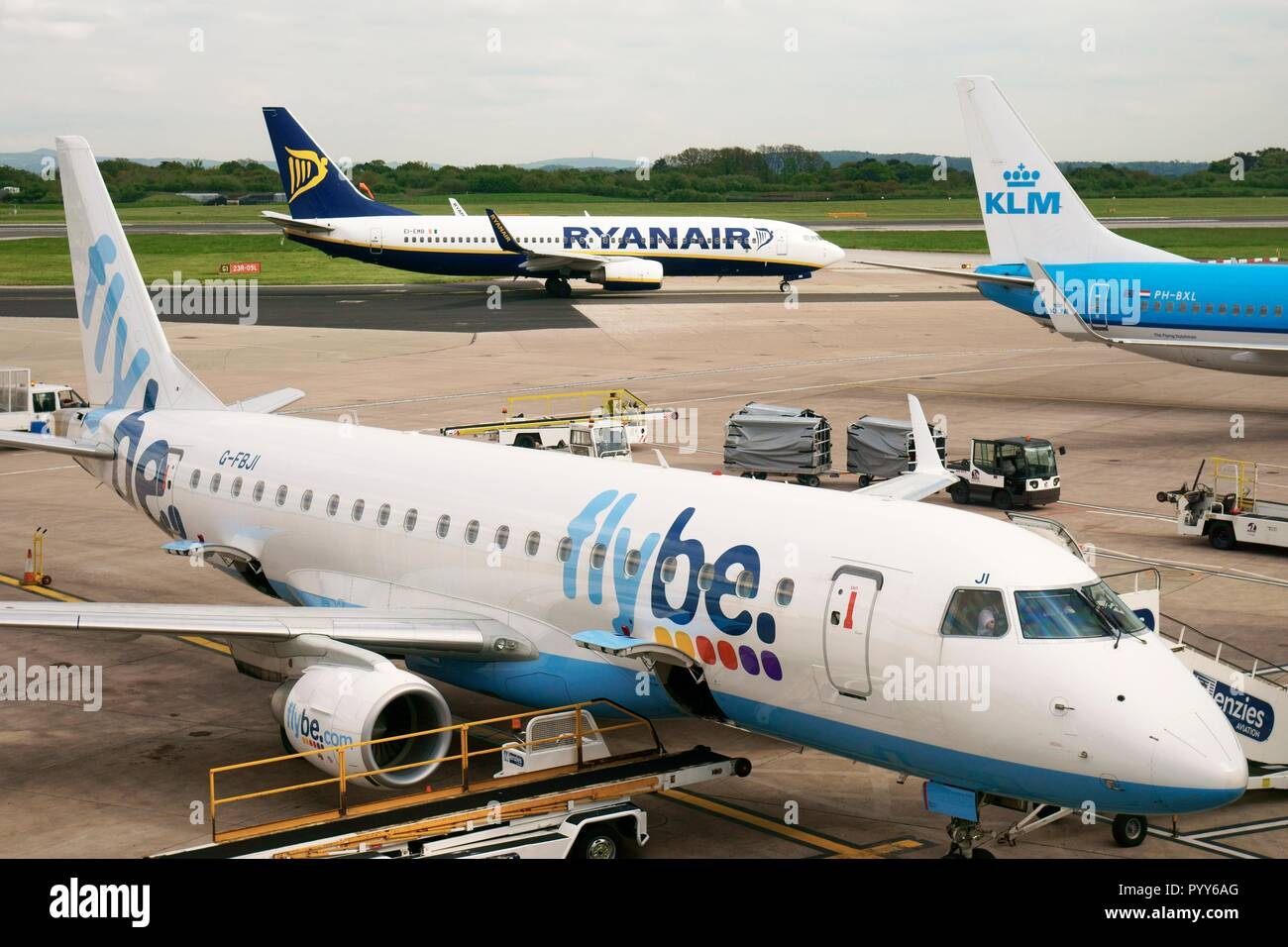 Flybe, Ryanair and KLM passenger plane jet aircraft airplane on runway apron seen from boarding gates of Manchester Airport Terminal Building, England Stock Photo
