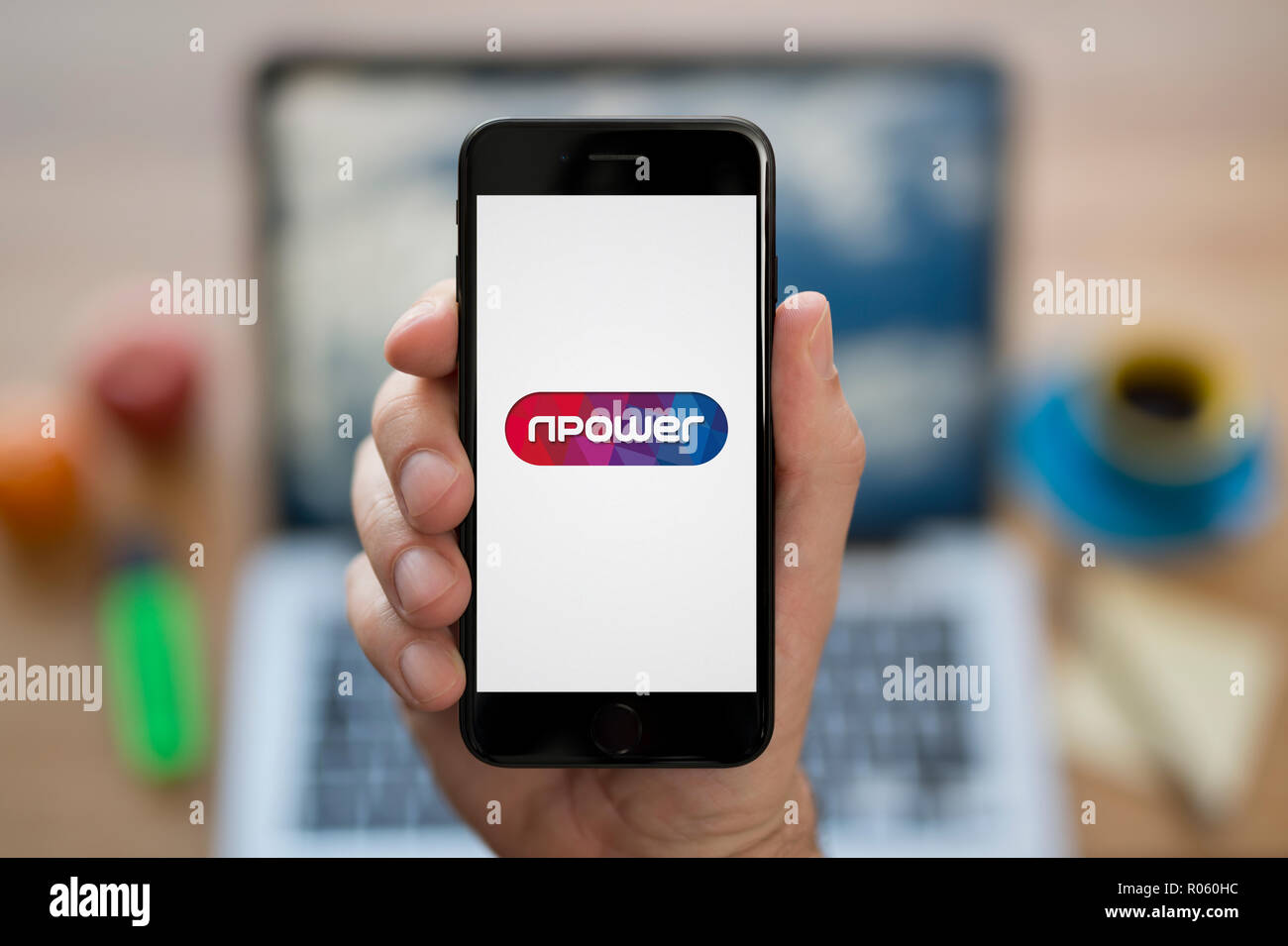 A man looks at his iPhone which displays the NPower logo, while sat at his computer desk (Editorial use only). Stock Photo