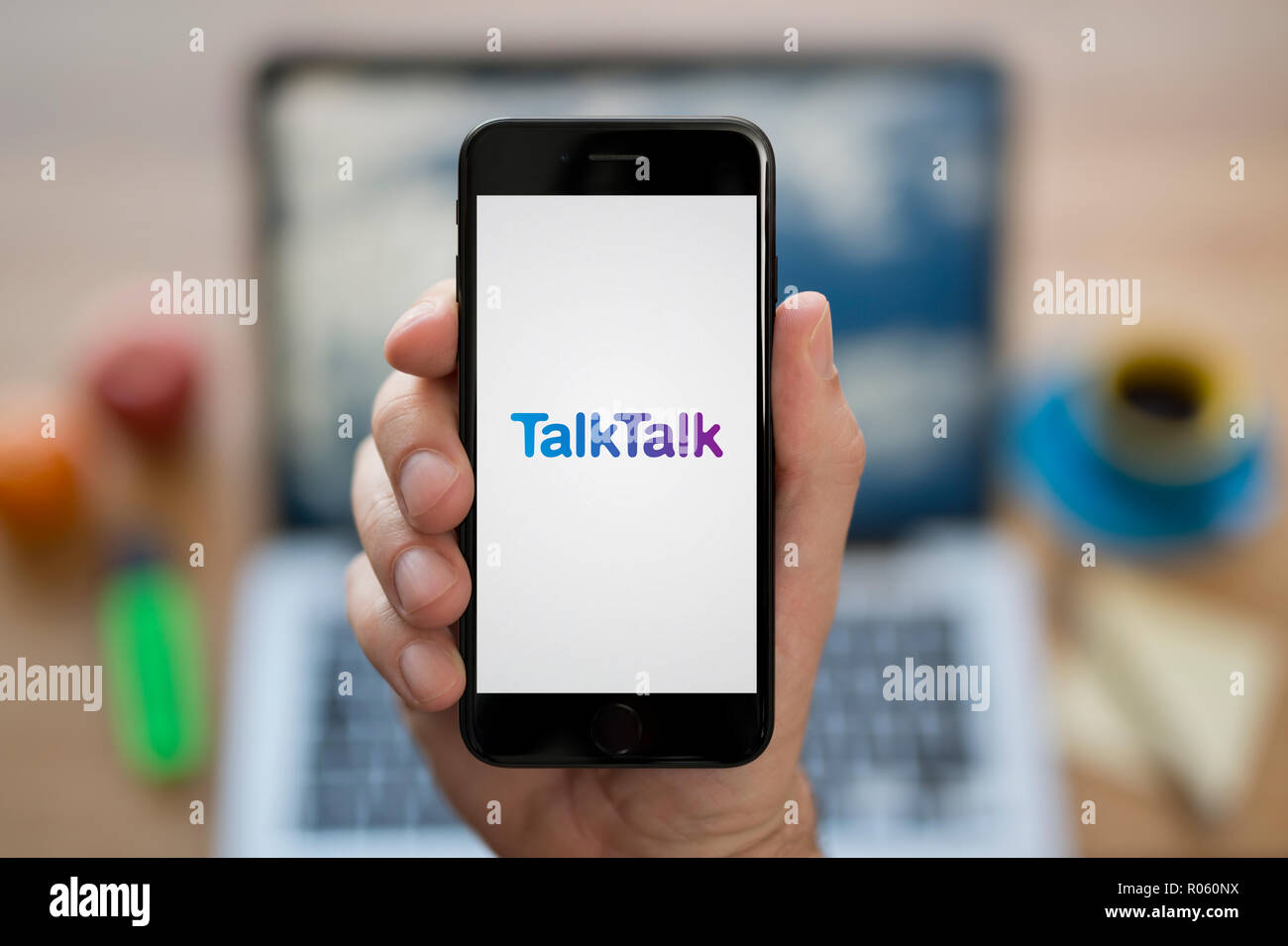 A man looks at his iPhone which displays the TalkTalk logo, while sat at his computer desk (Editorial use only). Stock Photo