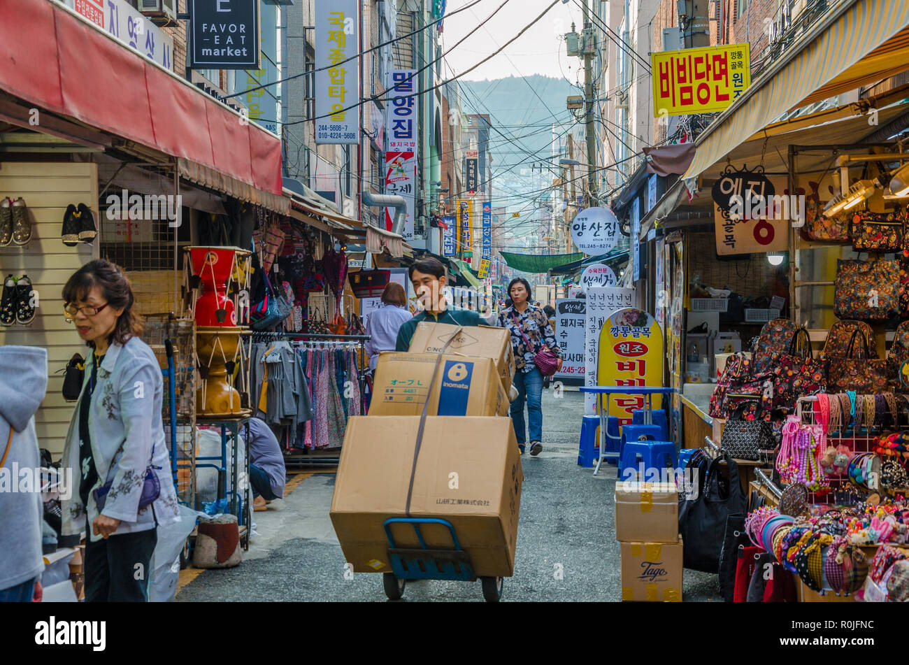 busy-street-market-scene-in-busan-south-korea-street-is-full-f-people-shopping-as-a-man-pushes-a-trolley-loaded-with-cardboard-boxes-R0JFNC.jpg