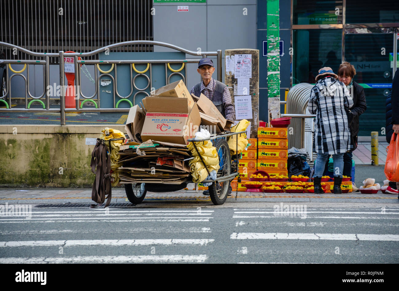a-man-pushes-a-cart-across-a-pedestrian-which-is-loaded-with-old-cardboard-boxes-R0JFNM.jpg