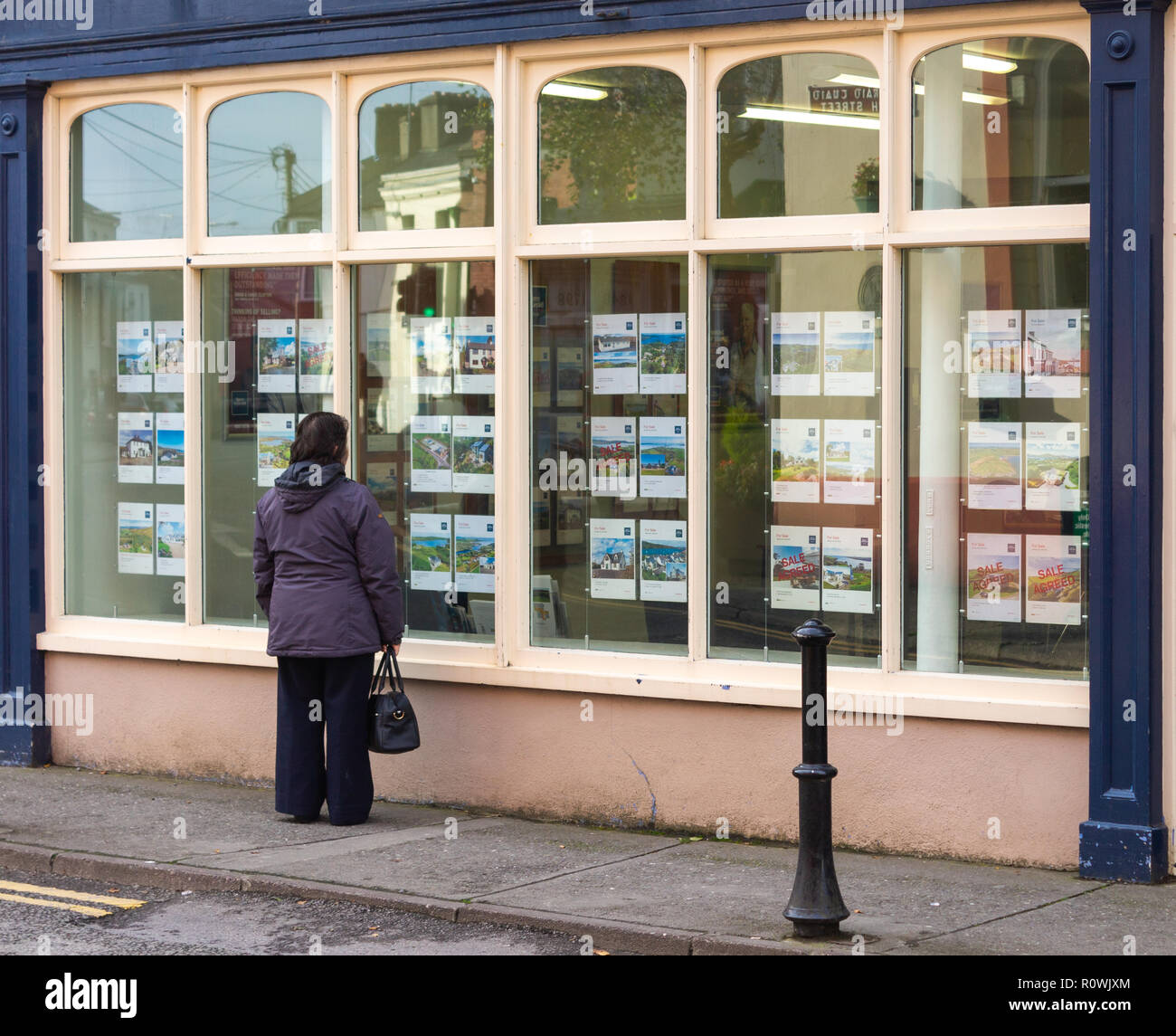 female-house-buyer-looking-at-estate-agents-property-for-sale-window-ireland-R0WJXM.jpg