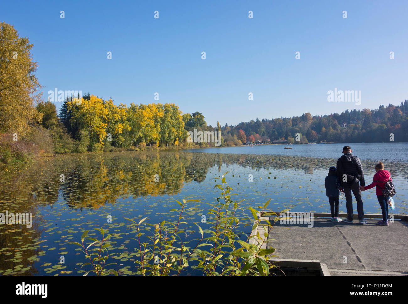Family of three at Deer Lake park in Burnaby, British Columbia, Canada. Stock Photo