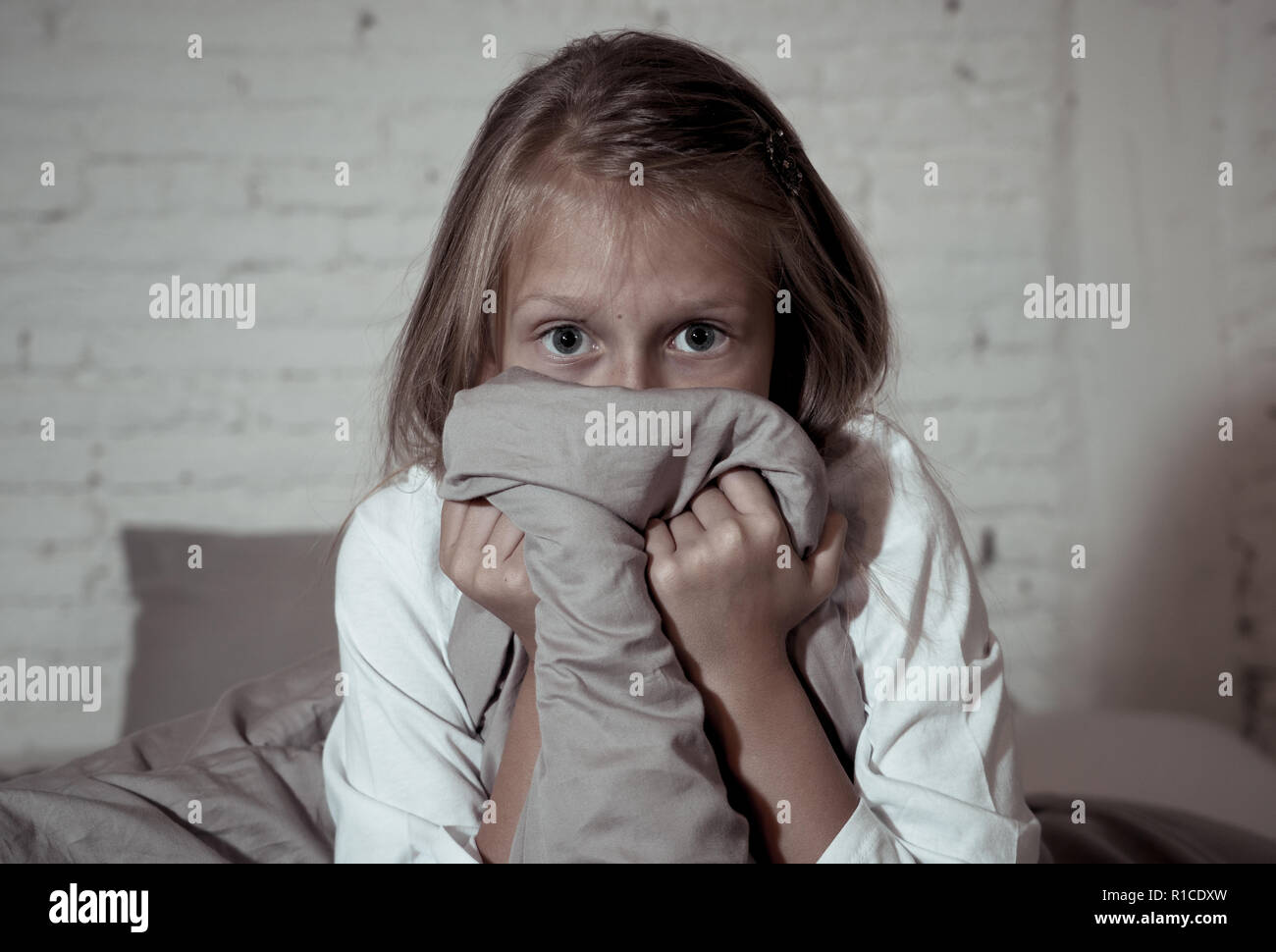 Scared little girl staying sleepless hiding behind the duvet looking horrified in the dark having childhood nightmares in child imagination Sleeping d Stock Photo