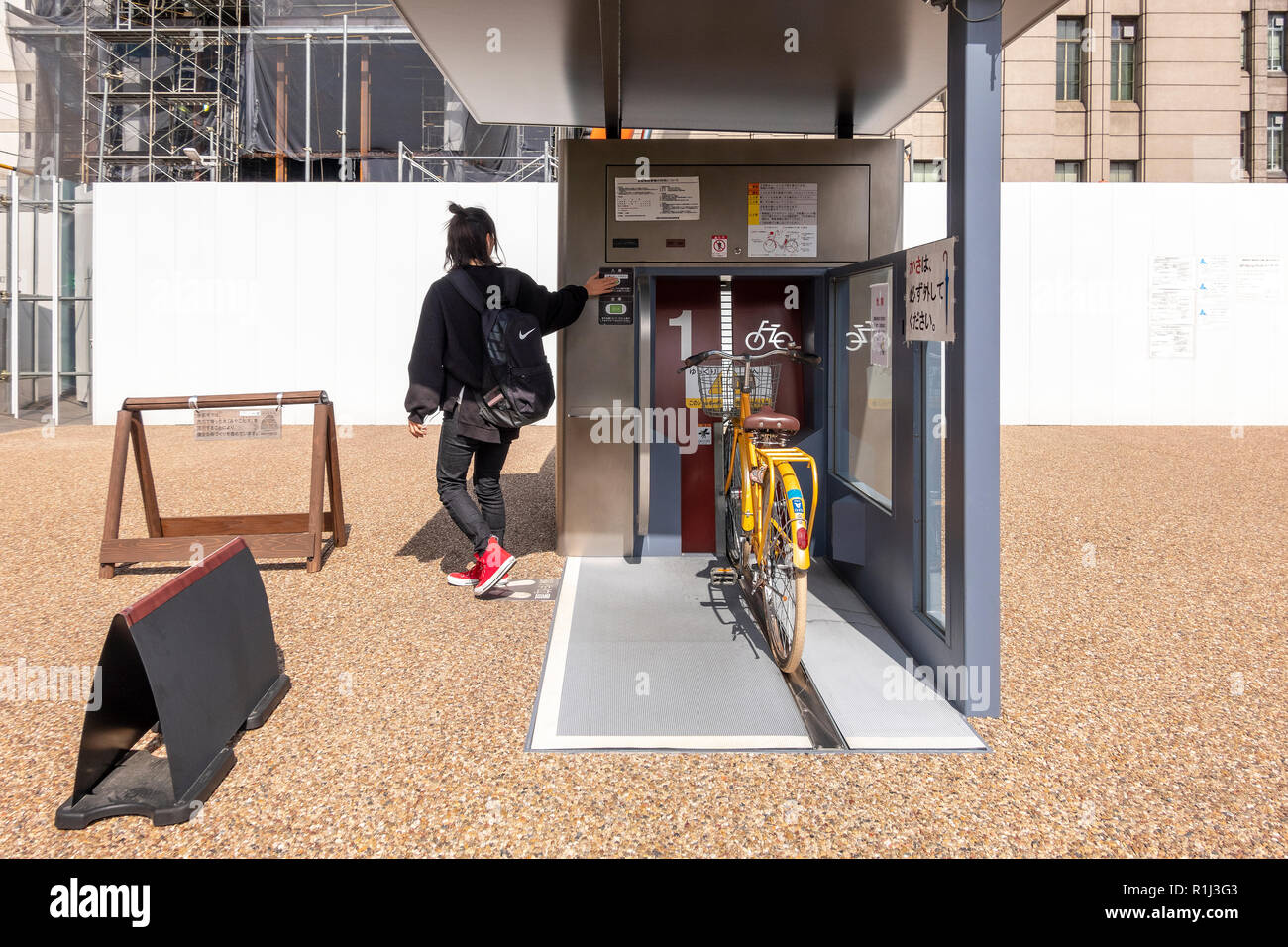 https://c7.alamy.com/comp/R1J3G3/girl-parking-her-bike-in-a-giken-eco-cycle-automated-underground-bicycle-parking-in-front-of-kyoto-city-hall-japan-series-of-3-images-R1J3G3.jpg