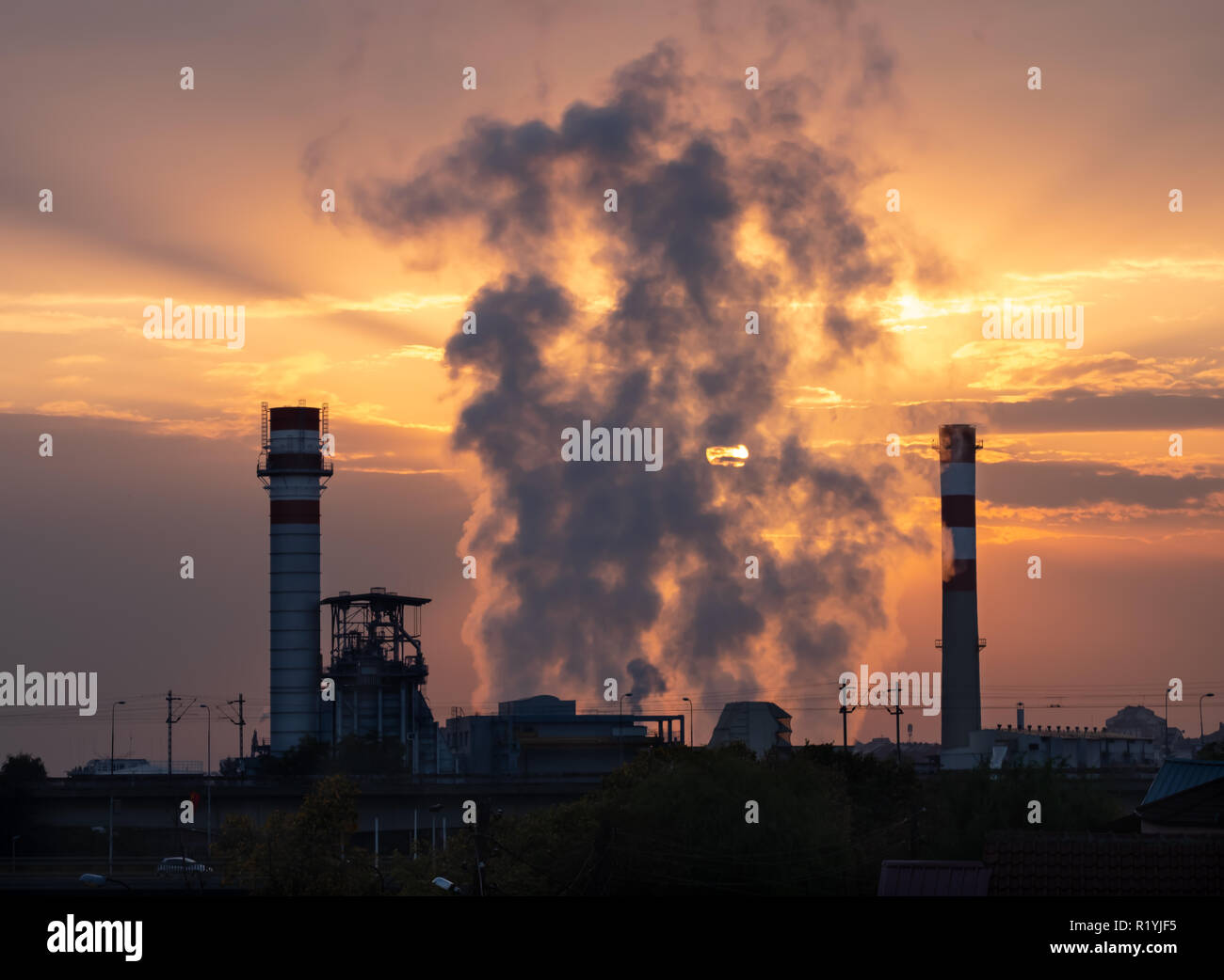 sunrise-over-industrial-factory-with-smoke-rising-between-smokestacks-behind-smoke-sun-and-orange-clouds-are-visible-R1YJF5.jpg