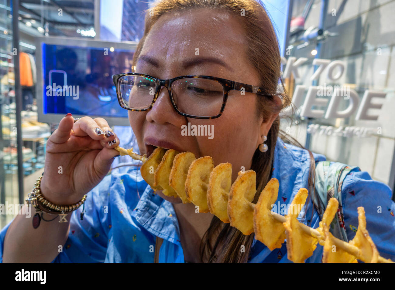 a-lady-eats-a-deep-fired-potato-spiral-on-a-stick-bought-form-a-street-food-stall-in-myeongdong-in-seoul-south-korea-R2XCM0.jpg