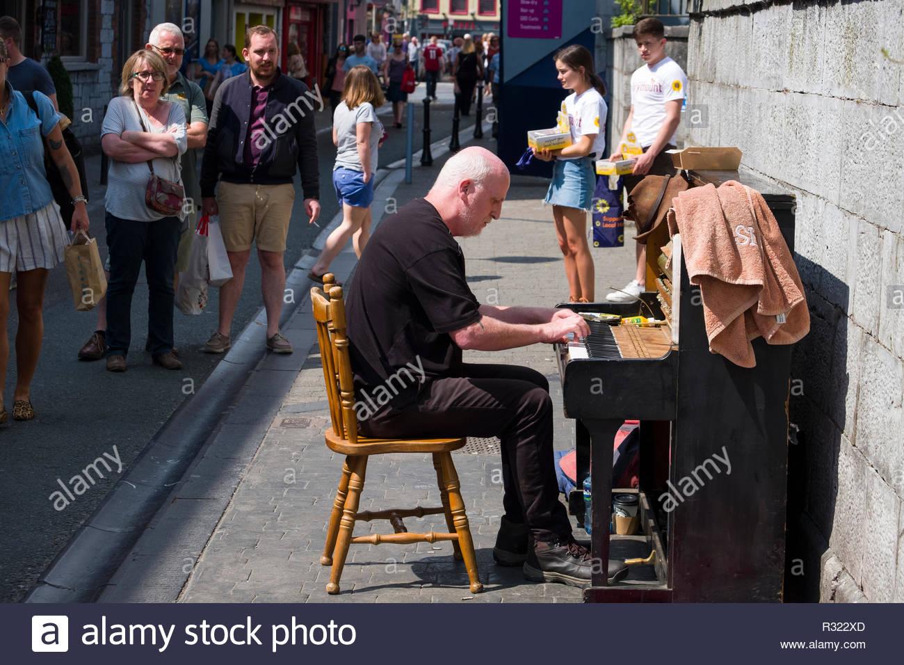 People watching man playing an upright piano outside on sidewalk, Paul Street, Centre, Cork, County Cork, Munster, Ireland Stock Photo