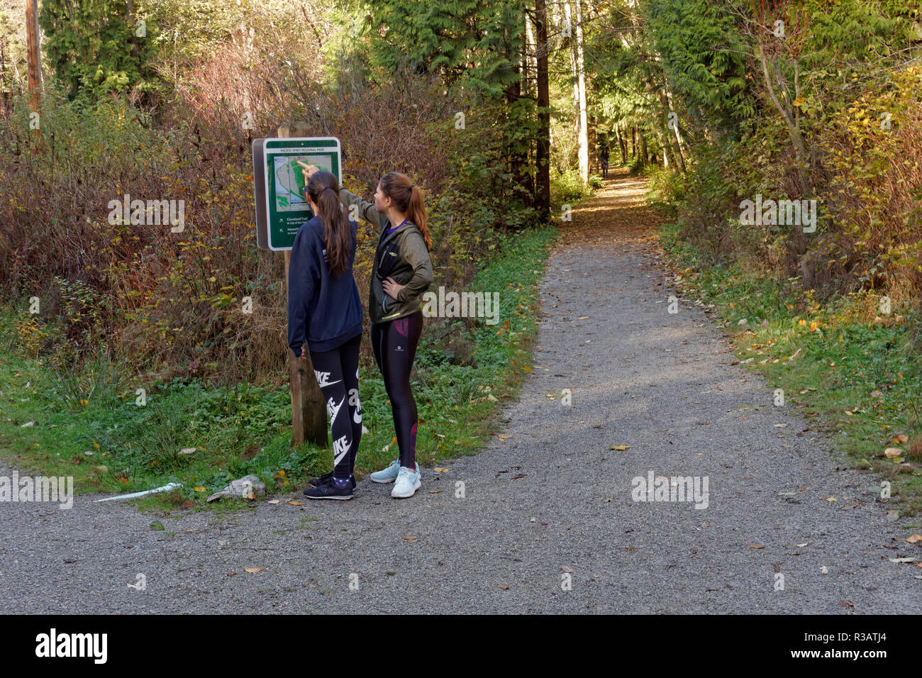 two-young-women-hikers-looking-at-a-trai
