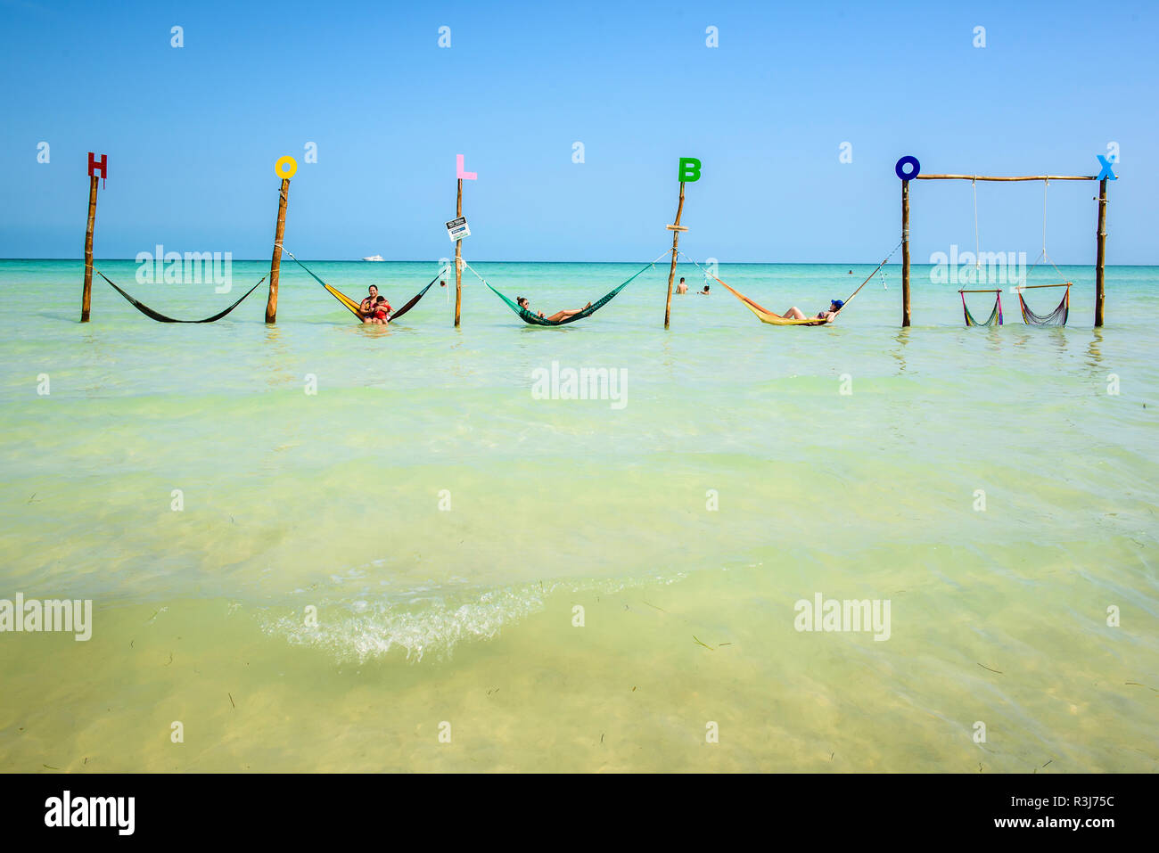 Tourists in hammocks on a beach, Isla Holbox, Quintana Roo, Mexico Stock Photo