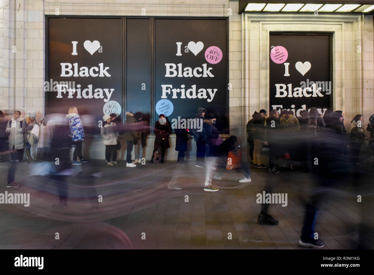 London, UK.  23 November 2018.  People queue into the night in front of advertising signs outside the UGG store near Piccadilly Circus on Black Friday.   Traditional retailers face increasing challenges to attract customers from their online competition. Credit: Stephen Chung / Alamy Live News Stock Photo