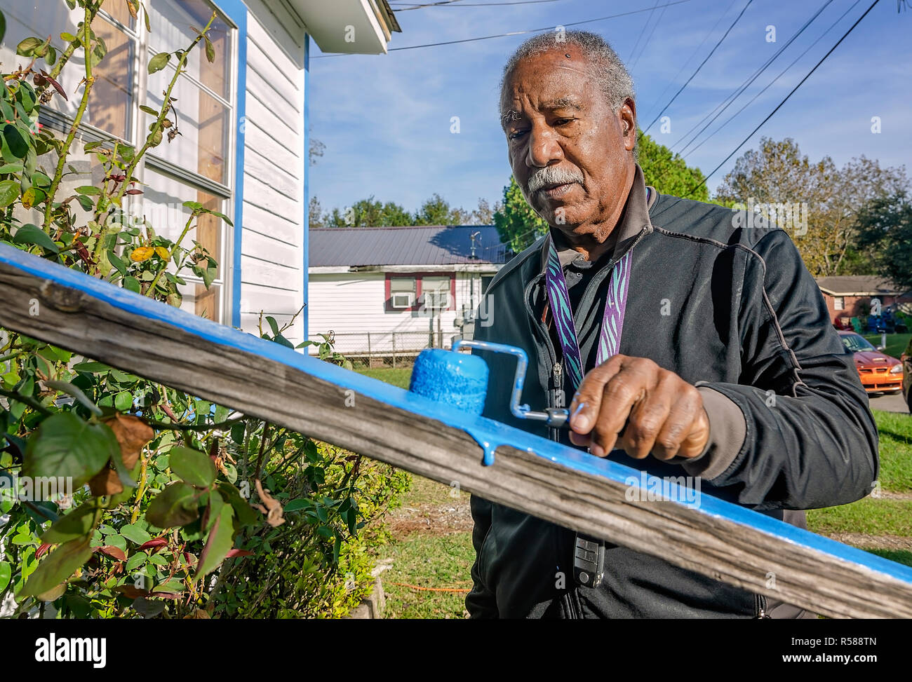 New York Mets Hall of Famer Cleon Jones paints a porch railing for a widow in his community, Nov. 21, 2018, in Mobile, Alabama. Stock Photo
