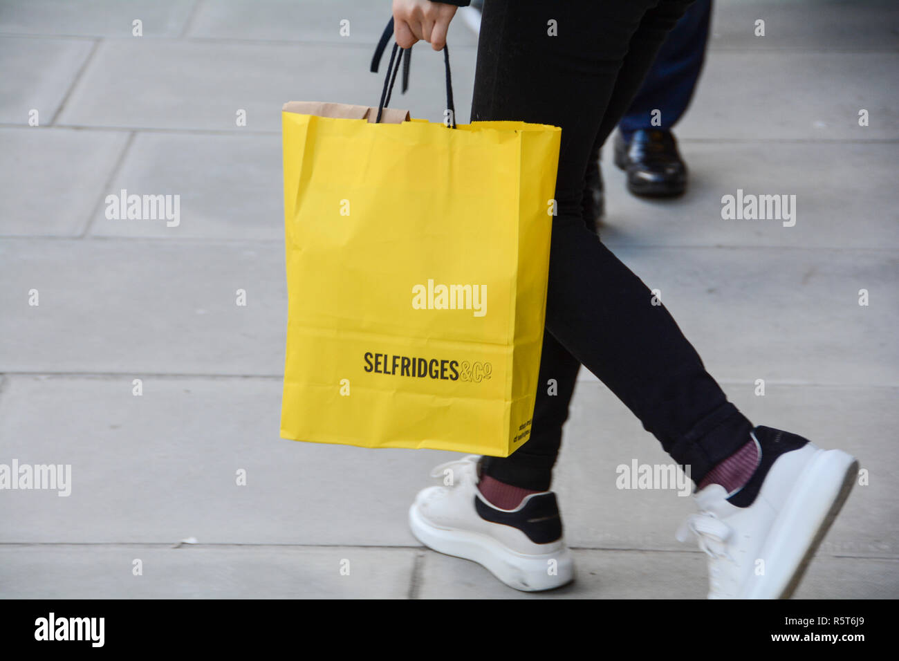 Close-up of a shopper carrying a Selfridges Department Store paper carrier bag on Oxford Street, London, England, UK Stock Photo