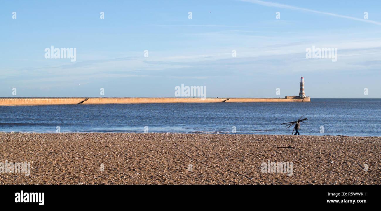 man-carrying-driftwood-roker-beach-sunde
