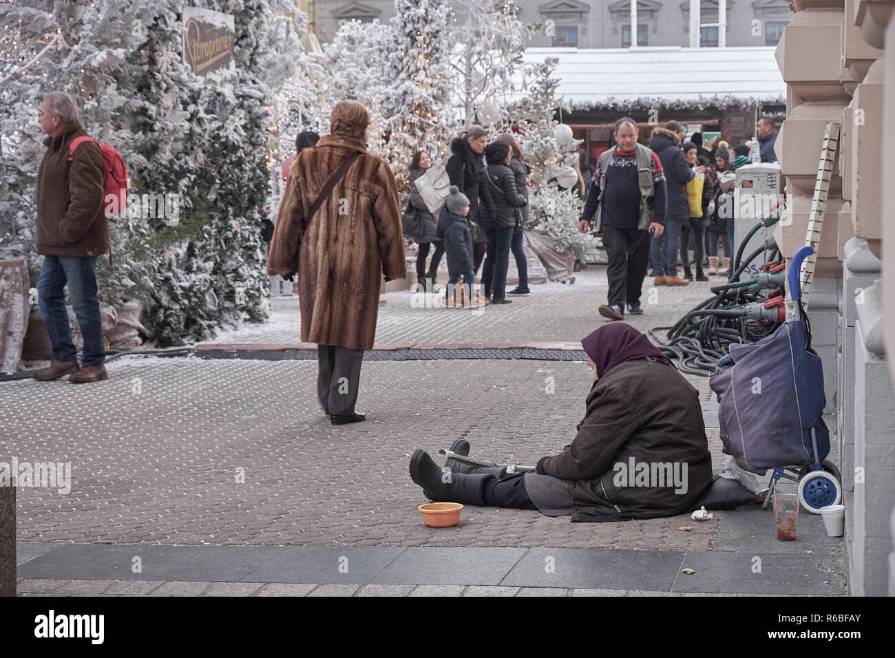 older-lady-sitting-on-ground-begging-passerby-in-zagreb-city-square-decorated-during-celebrations-of-advent-market-happen-walkers-mostly-ignoring-R6BFAY.jpg