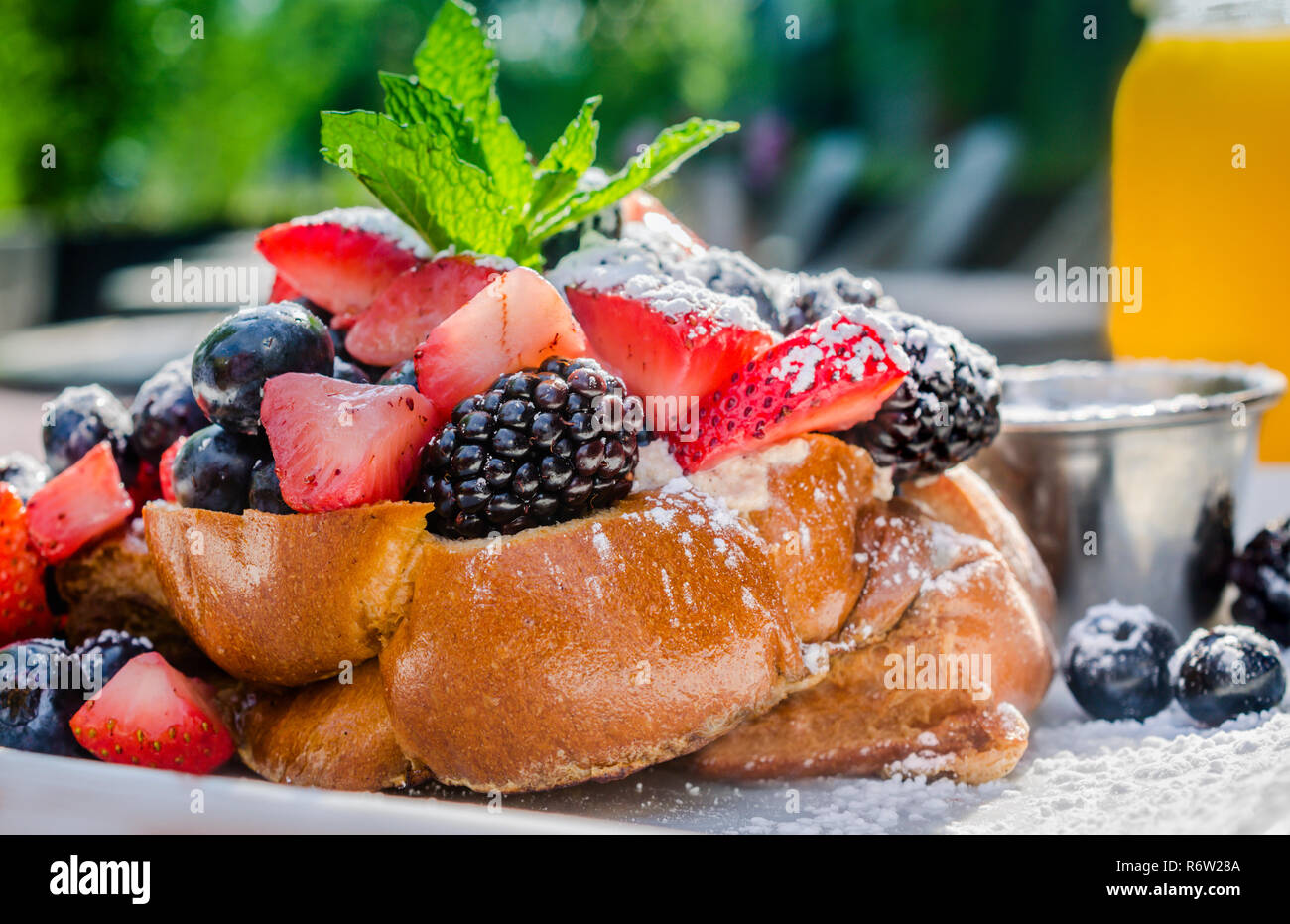 Challah French toast stuffed with honeyed ricotta, topped with fruit, powdered sugar, and maple syrup at Sun in My Belly Cafe in Atlanta, Georgia. Stock Photo