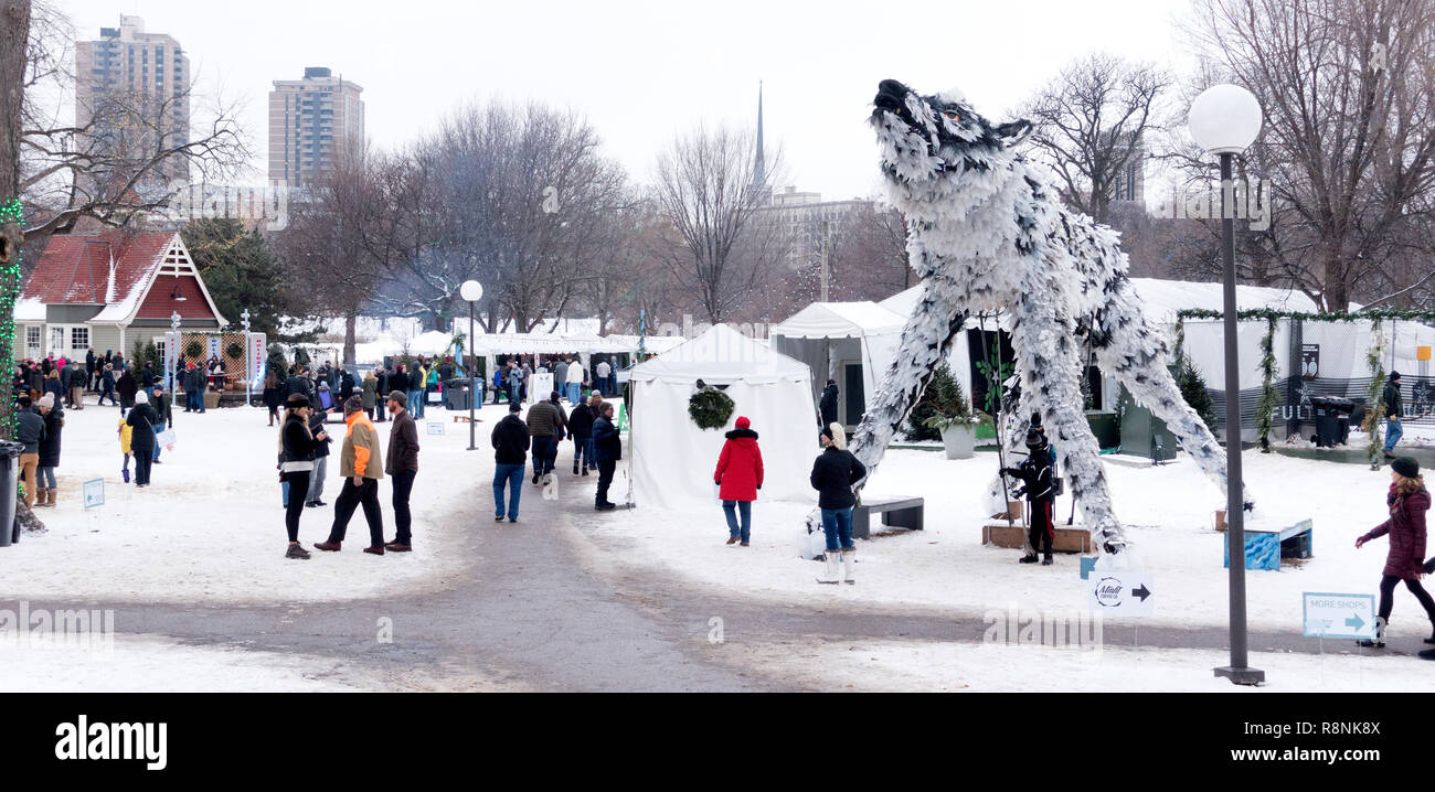 Art sculpture of large wolf made from 90% recycled materials overlooking people having fun at Holidazzle in Loring Park. Minneapolis Minnesota MN USA Stock Photo