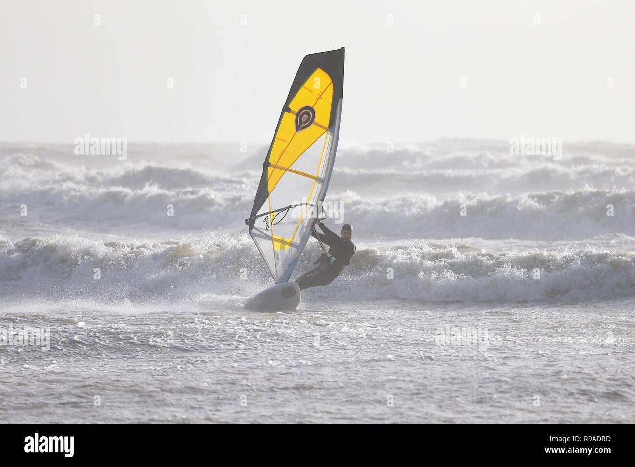 Camber, East Sussex, UK. 21st Dec, 2018. UK Weather: These kite surfers make the most of the ideal conditions to kite surf with gale force winds exceeding 40mph. This wind surfer gets a piece of the action as well. © Paul Lawrenson 2018, Photo Credit: Paul Lawrenson/ Alamy Live NewsStock Photo