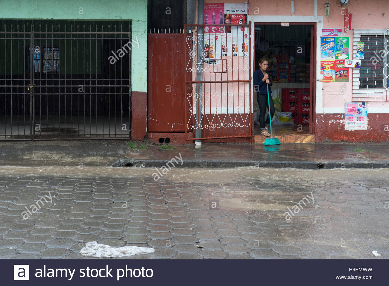 Woman watches tropical rain come down hard in Jinotega, Nicaragua.  Water is running high in the gutter. Stock Photo