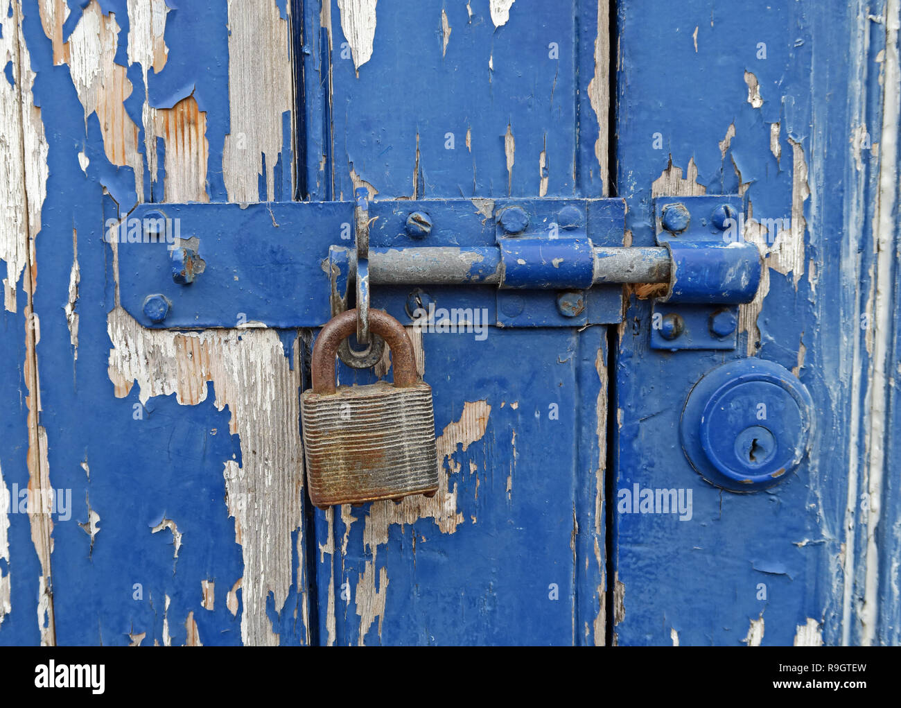 GoTonySmith,@HotpixUK,HotpixUK,Blue bolted door with peeling paint,South West England,UK,security,old,old lock,history,weathered,peeling,paint,weathered peeling,peeling paint,colour,colours,cracked,distressed,colored,key,keyhole,rust,rustic,deprivation,deprived,flakes,flaking,screws,door furniture,old door,neglected,unloved,garage,wooden,wood,hasp,old hasp,shut up