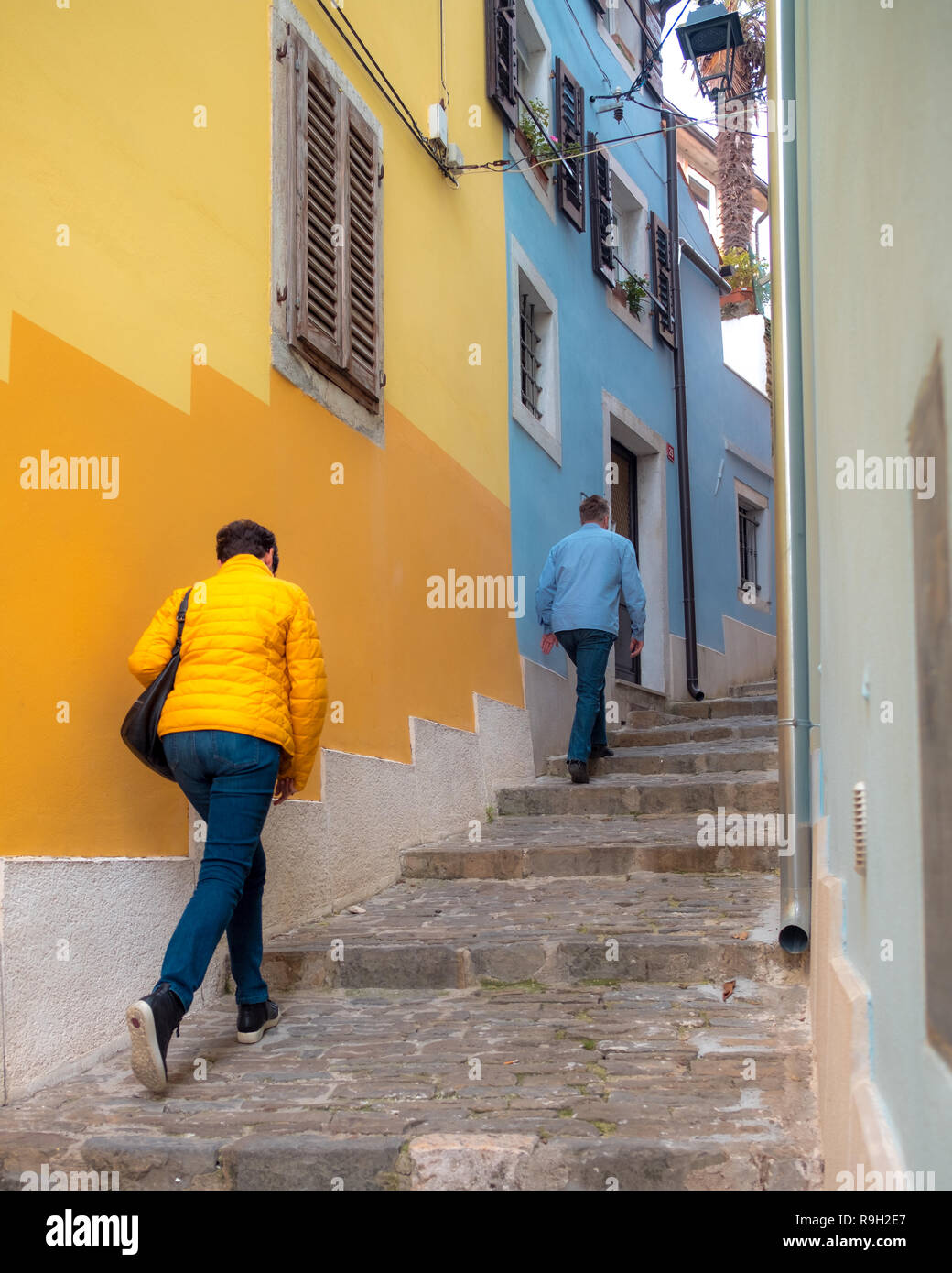 colorful-street-staircase-of-the-istrian-town-of-piran-with-2-walkers-with-jackets-matching-wall-colors-R9H2E7.jpg