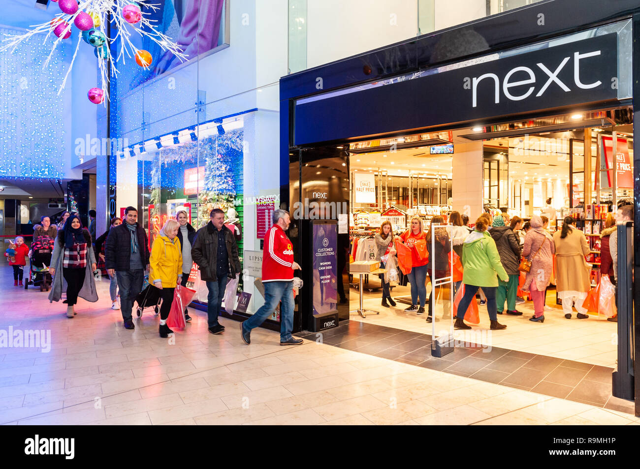 Blackpool, Lancashire,  UK. 26th Dec, 2018. Shoppers rush into the Next store for the 6am sale with large plastic bags given to them by staff so store supervisors can see their purchases. With some people claiming they queued from 2am, there was approximately 120 bargain hunters waiting for the shop to open at 6am. Shop staff say this was the biggest queue in a number of years.  Credit: Andy Gibson/Alamy Live News. Stock Photo