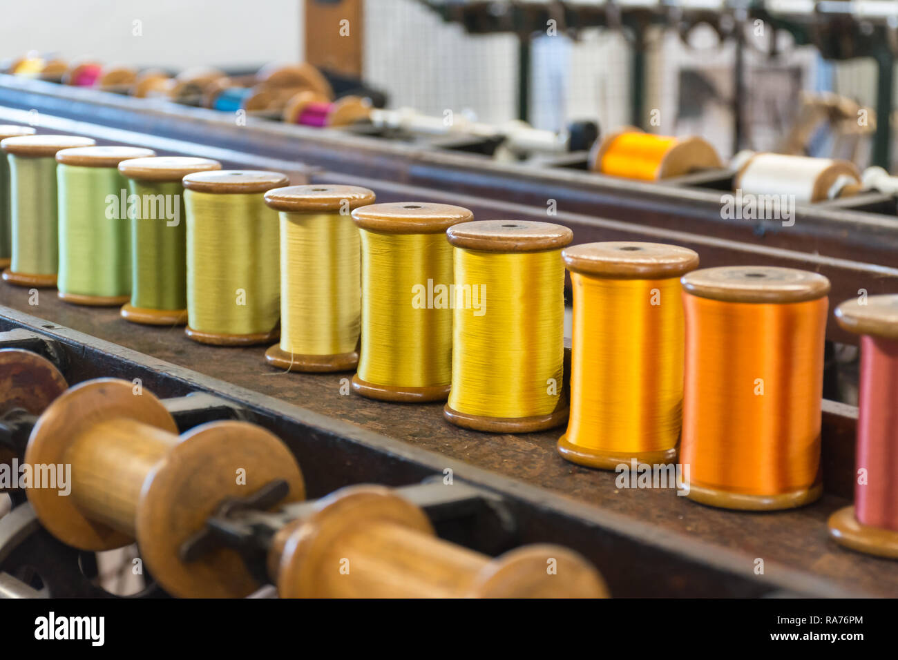 whitchurch-silk-mill-in-hampshire-uk-close-up-of-colourful-silk-yarn-on-bobbins-ready-for-spinning-RA76PM.jpg
