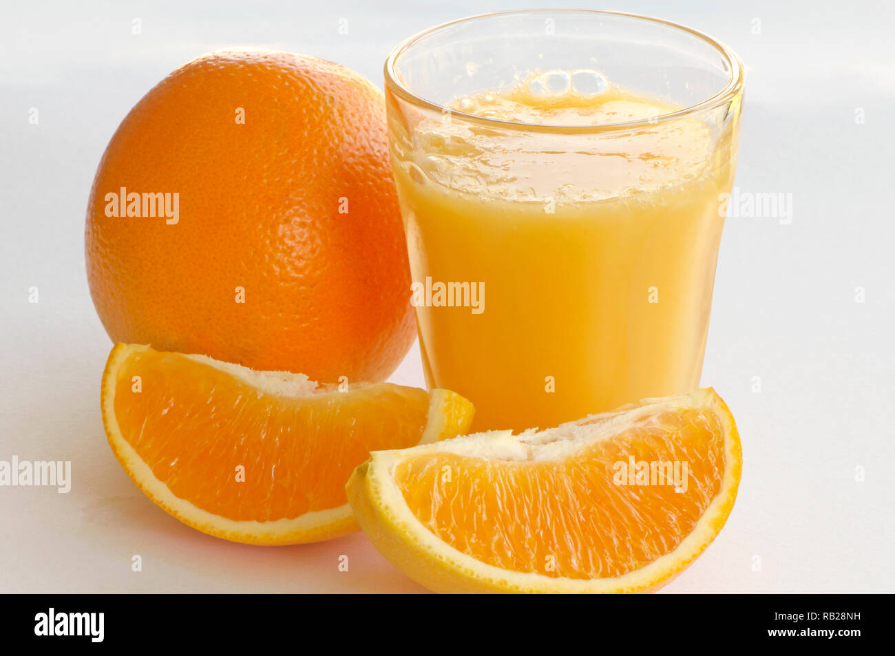 a-glass-of-orange-juice-with-a-whole-navel-orange-citrus-x-sinensis-and-two-orange-wedges-on-a-white-background-RB28NH.jpg