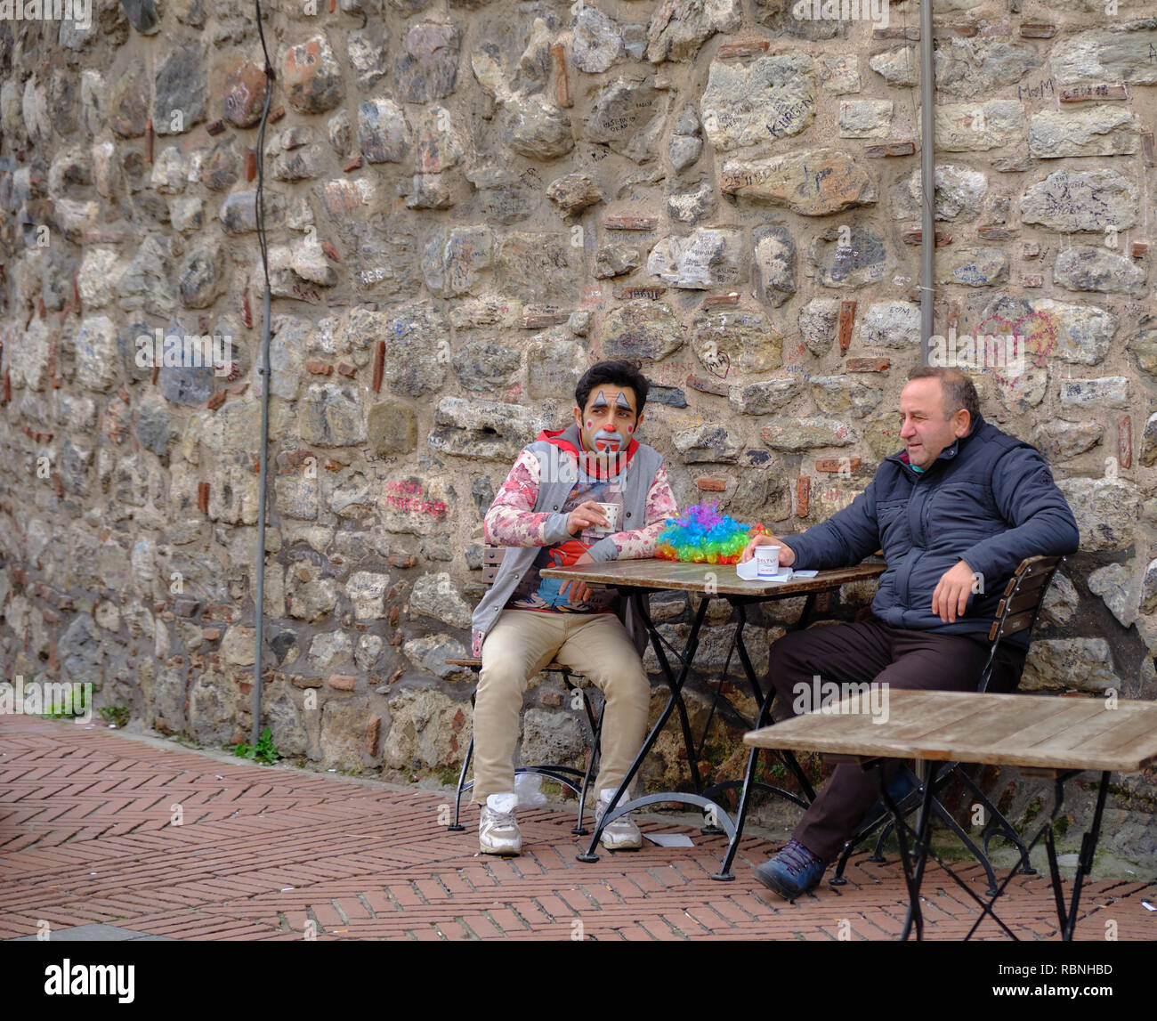 istanbul-clown-having-removed-wig-but-still-with-facial-make-up-sits-down-to-have-a-coffee-with-older-gentleman-by-galata-tower-RBNHBD.jpg