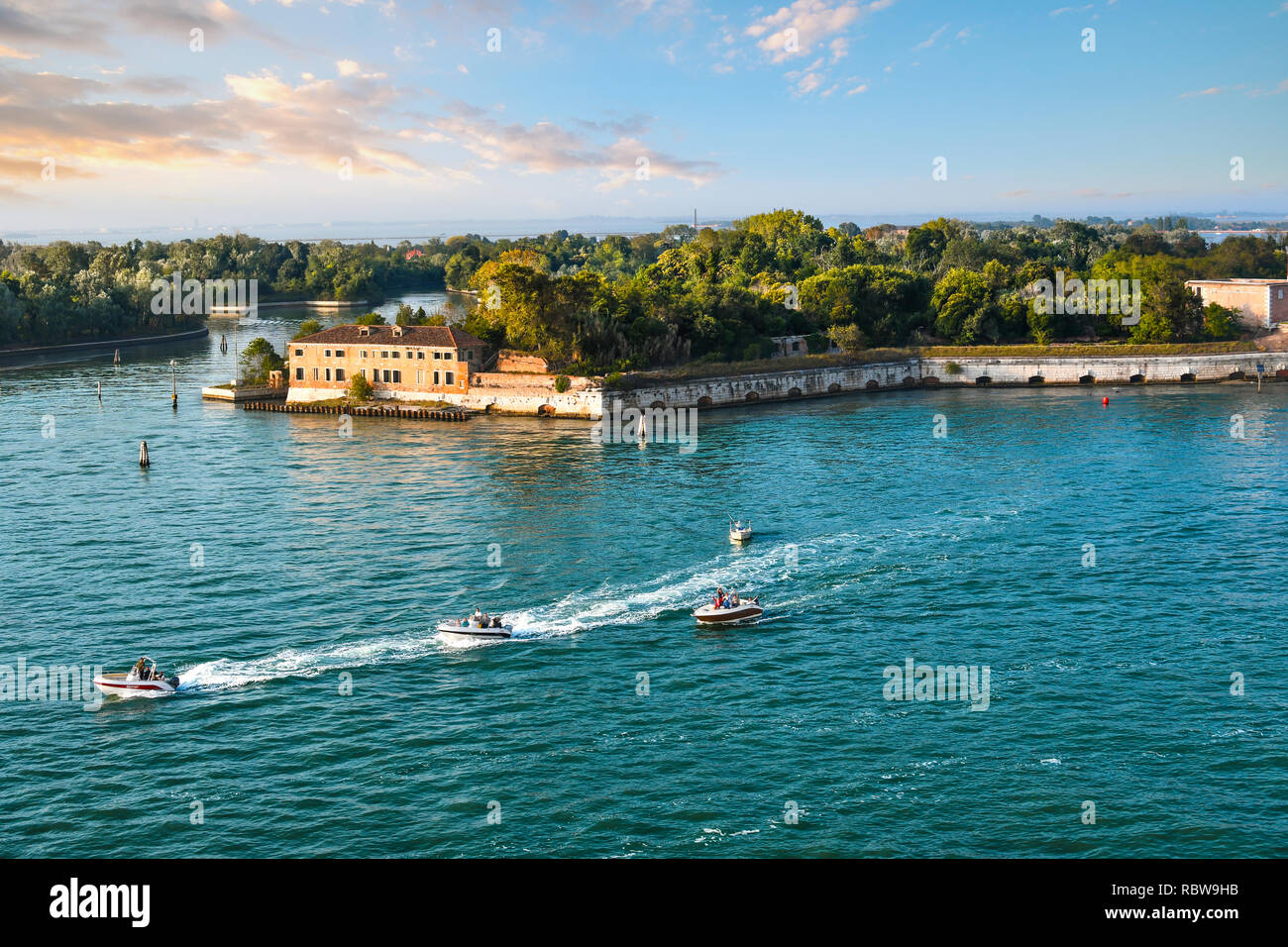 a-group-of-small-motor-boats-cruise-past-one-of-the-outlying-islands-near-poveglia-in-the-waters-off-of-venice-italy-RBW9HB.jpg