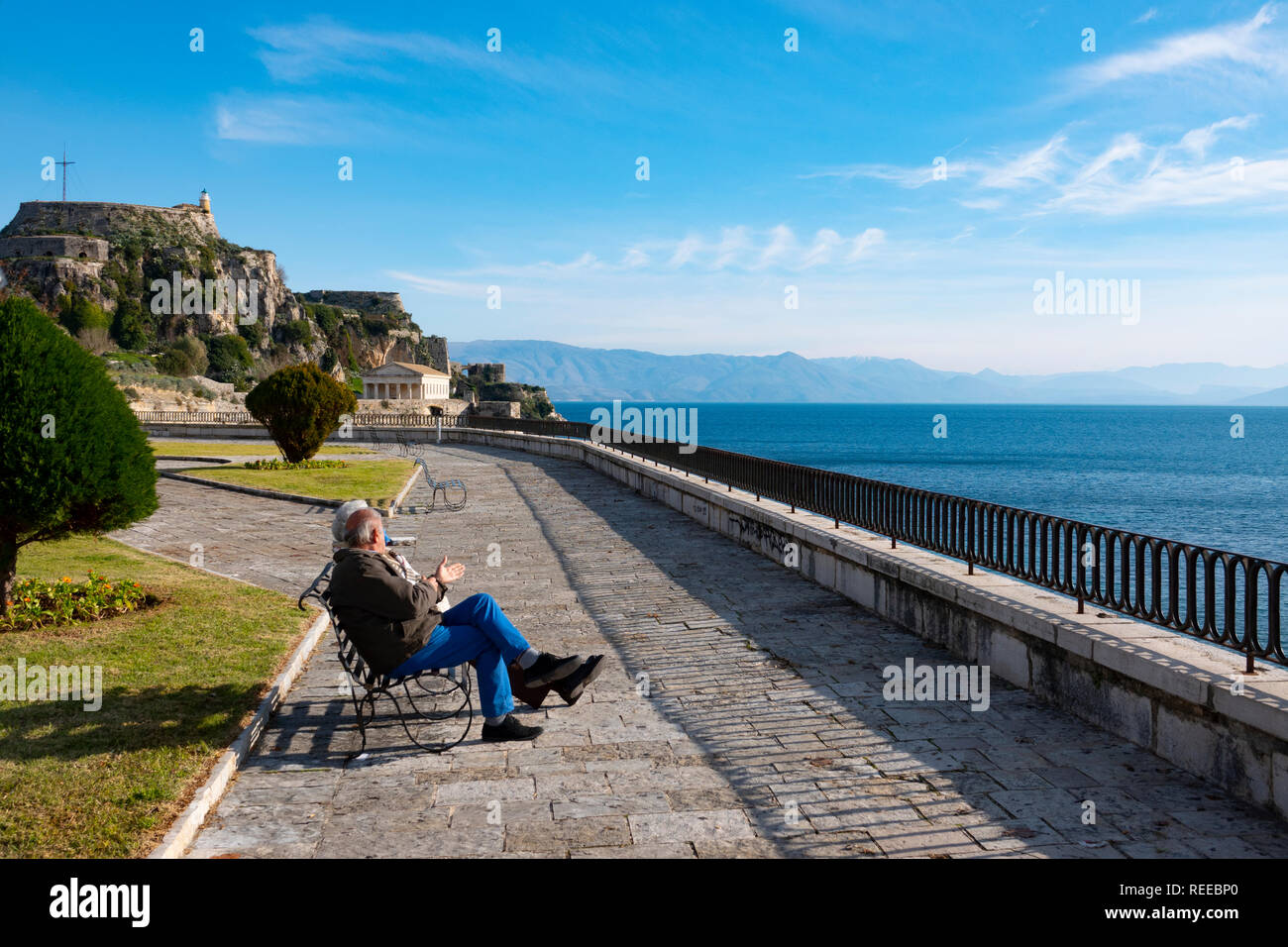 greece-corfu-corfu-town-an-elderly-couple-sits-along-the-seafront-near-the-old-fortress-taking-in-the-sun-REEBP0.jpg