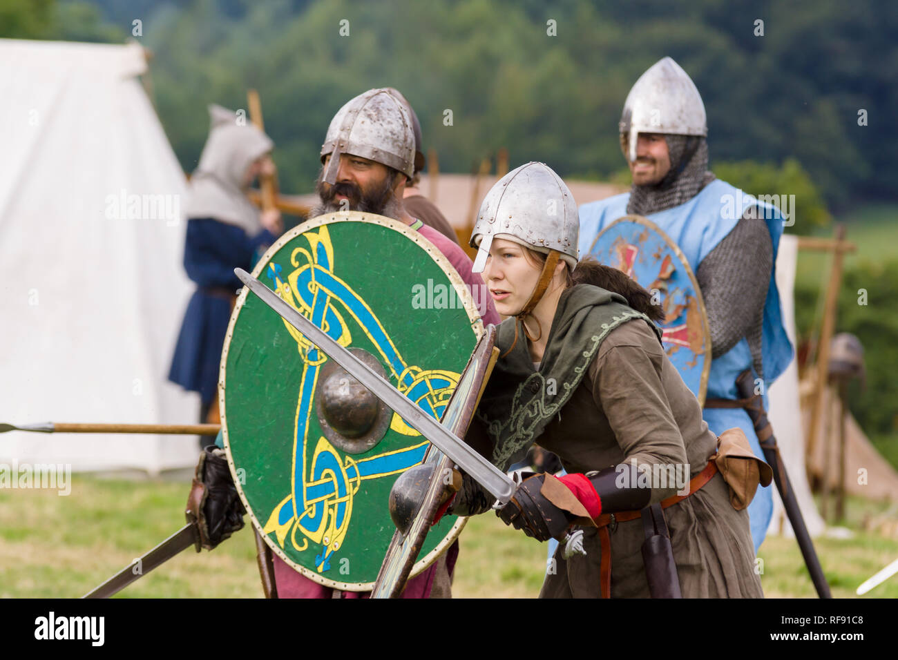 Medieval re-enactors dressed in armour and costumes of the 12th century equipped with swords and shields re-enacting combat of the period Stock Photo