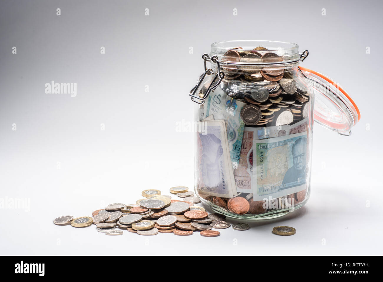 Savings UK - a glass storage jar completely full of british coins and notes, saved up.  Concept illustration for pension planning, rainy day fund, emergency money, home banking, cash in hand, accumulated wealth Stock Photo
