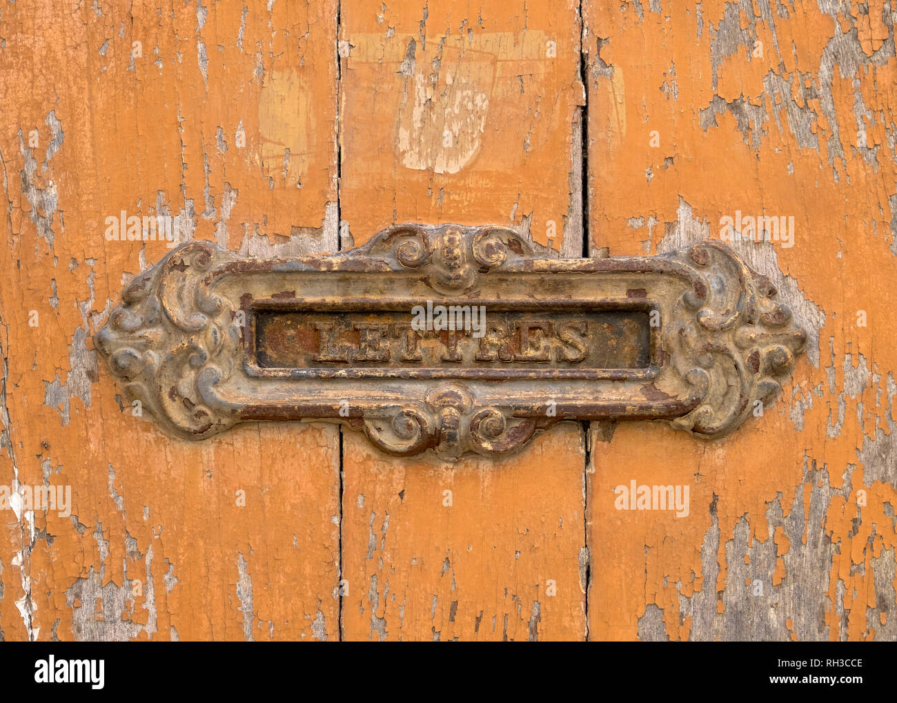 rusted-old-french-letter-slot-on-orange-peeling-wood-door-writing-in-french-lettres-RH3CCE.jpg