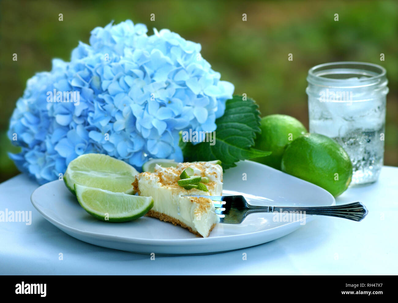Key lime pie, served outside with lime slices and water, makes a cool summer treat in the Deep South. Stock Photo