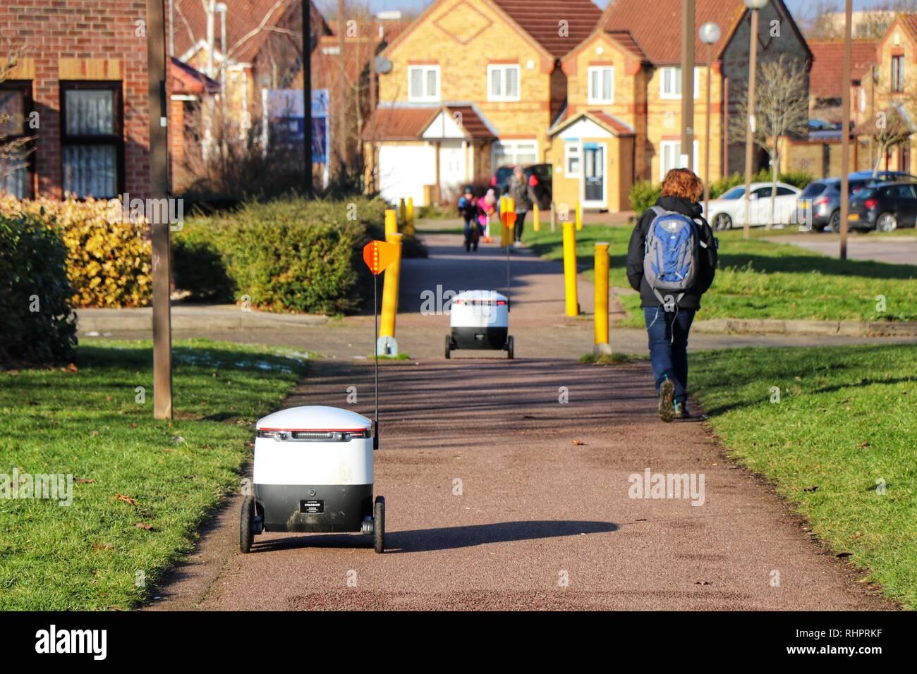 Pedestrians go about their daily lives as Starship Technologies autonomous robots make routine grocery deliveries around Milton Keynes. Stock Photo