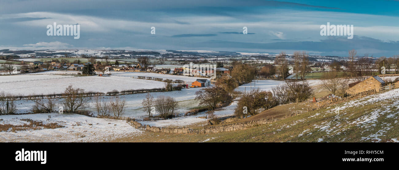 teesdale-landscape-panoramic-view-over-the-rural-village-of-hutton-magna-towards-barningham-moor-with-snow-covered-fields-dark-sky-and-sunshine-RHY5CM.jpg