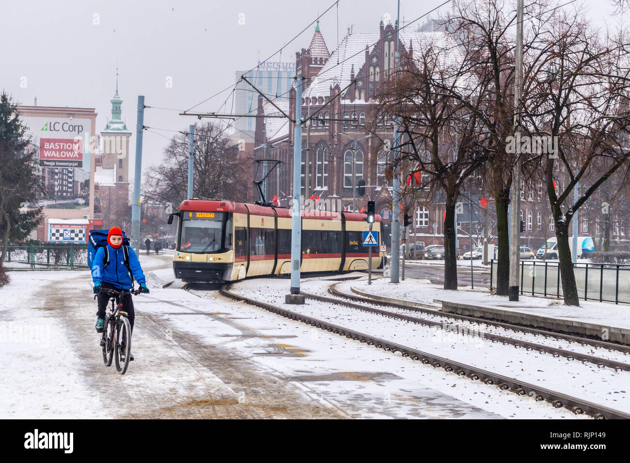 a-man-on-a-bicycle-with-a-tram-approaching-in-snow-plac-solidarnisci-gdask-poland-RJP149.jpg