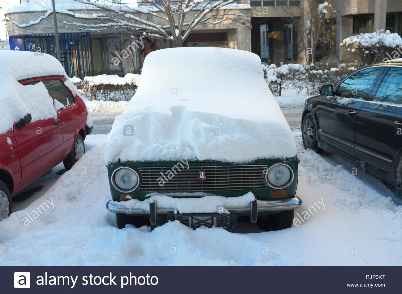 An old Lada car is submerged under recent heavy snowfall in the city of Novi Sad, Vojvodina, Serbia. Stock Photo