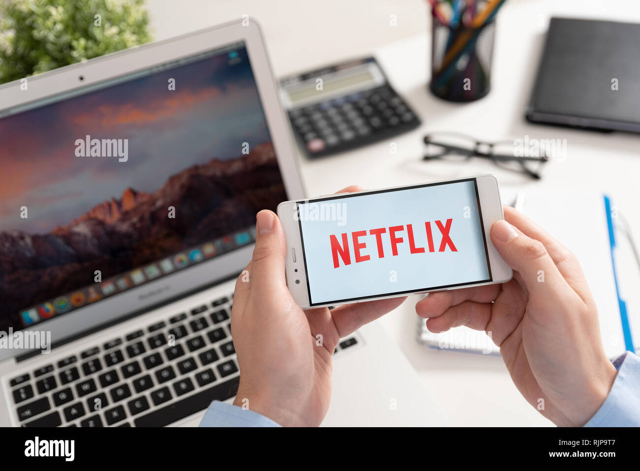 Wroclaw, Poland - JAN 31, 2019: Man holding smartphone with Netflix logo. Netflix is a global provider of streaming movies and TV series Stock Photo