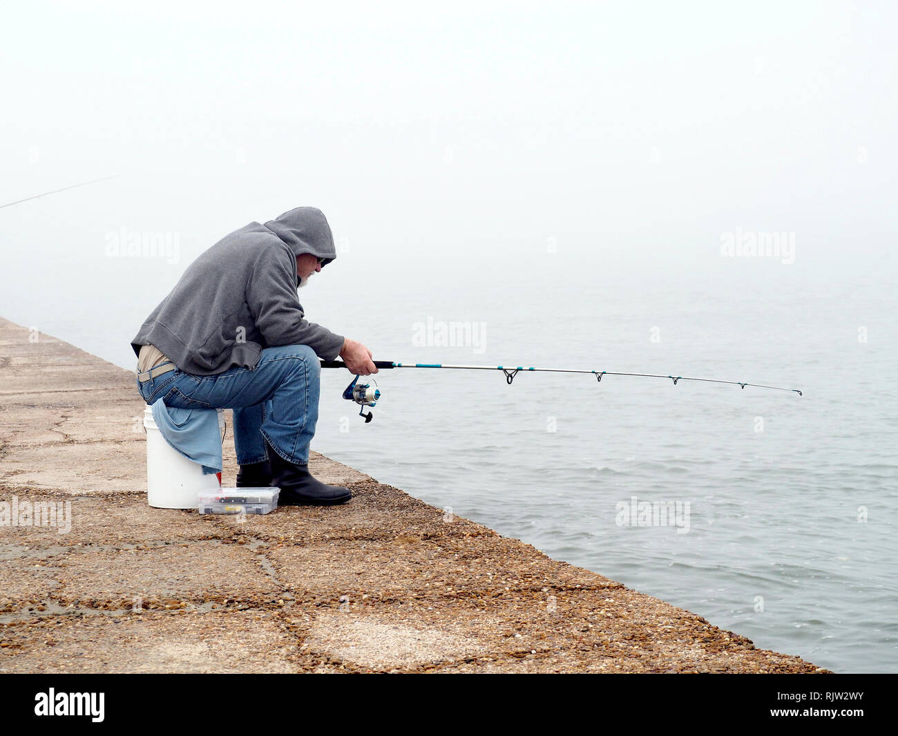 an-old-man-in-blue-jeans-and-gray-hooded-sweat-shirt-sits-on-a-five-gallon-bucket-while-fishing-on-a-foggy-day-south-jetty-port-aransas-texas-usa-RJW2WY.jpg